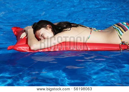 A very attractive young woman taking a sunbath on her red airbed