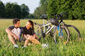 stock photo of beside  - Happy Young Sportive Couple Sitting On Grass Besides Bicycles - JPG