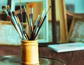 stock photo of acrylic painting  - Close up of painting brushes in studio of artist - JPG