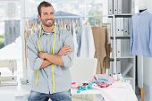 stock photo of cross-dress  - Smiling handsome male fashion designer with arms crossed in the studio - JPG