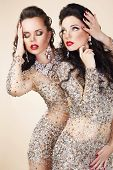 foto of opulence  - Two Glamorous Women in Evening Dresses and Jewelry Dancing - JPG