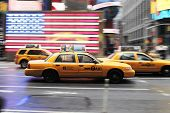 NEW YORK CITY, USA - JUNE 12: Yellow taxi cab speeding through Times Square. A US flag in the backgr
