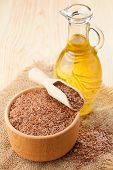 foto of flax seed oil  - mortar of flax seeds with wooden scoop and linseed oil in glass jug - JPG