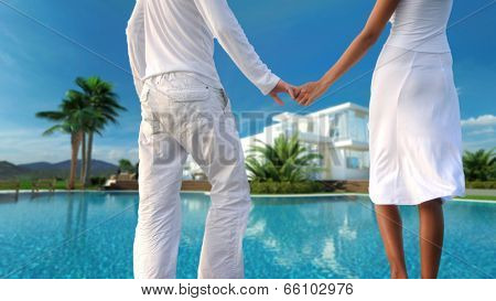 View from behind of a romantic couple standing holding hands overlooking their dream modern whitewashed tropical villa and sparkling swimming pool, torsos only in a conceptual image