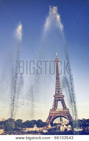 View of the Eiffel Tower, Paris, France through the arching sprays of water on the fountains in the park below on a hot sunny day