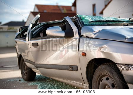 Totally destroyed silver sedan motor car in a traffic accident with a flattened roof, shattered windows and crumpled bodywork