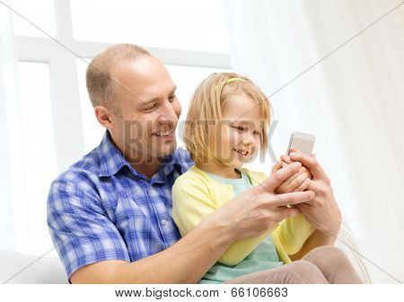 family, children, parenthood, technology and internet concept - happy father and daughter with smartphone at home