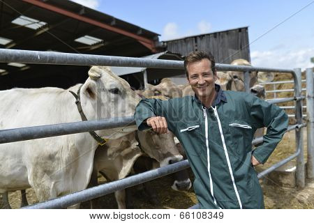 Portrait of smiling farmer standing by barn