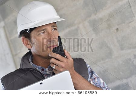 Entrepreneur on building site using walkie talkie