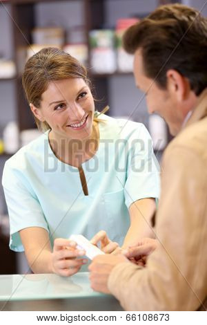 Pharmacist giving advice to customer on medication