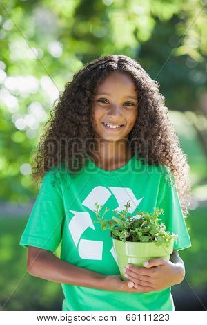 Young environmental activist smiling at the camera holding a potted plant on a sunny day