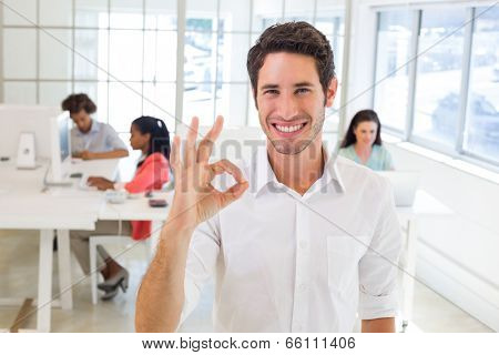 Worker giving an OK gesture in the office