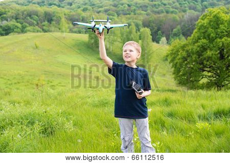 Happy boy with plane on a meadow in a sunny day. Smiling young boy preparing to launch RC plane.
