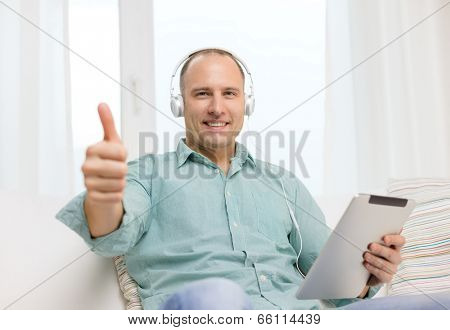 technology and lifestyle, distance learning concept - handsome man with tablet pc computer and headphones at home showing thumbs up