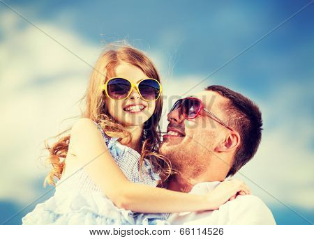 summer holidays, children and people concept - happy father and child in sunglasses over blue sky