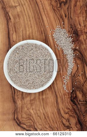 White chia seed in a porcelain dish on an olive wood board. Salvia hispanica.