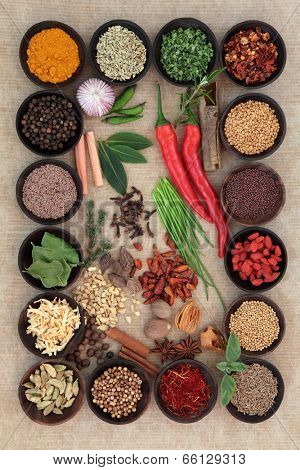 Large spice and herb collection in wooden bowls and loose.