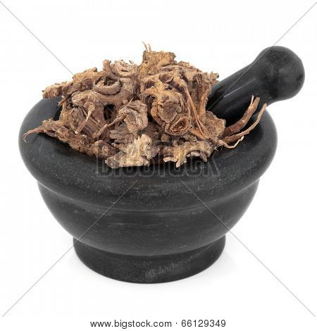 Lovage ligusticum root herb chinese herbal medicine in a black stone mortar with pestle over white background. Gao ben.