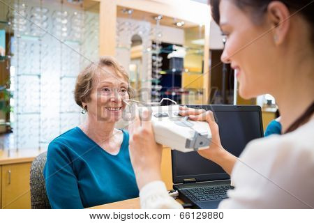 Happy senior woman getting an eye test from ophthalmologist in store