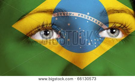 Portrait of a woman with the flag of the Brazil painted on her face