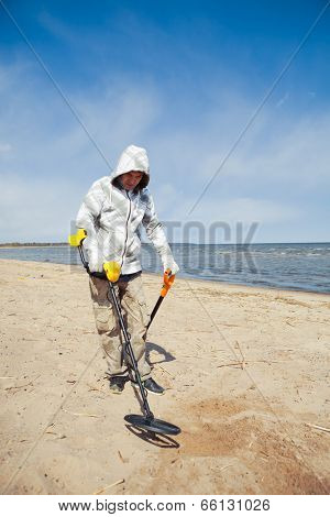 man searching for a precious metal using a metal detector
