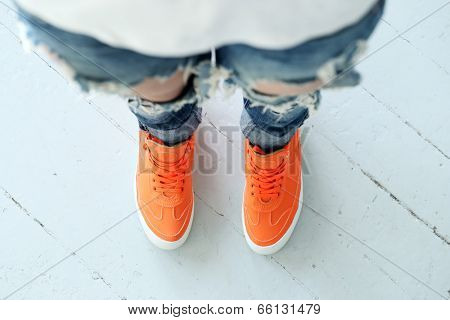 Woman wearing torn jeans and orange boots