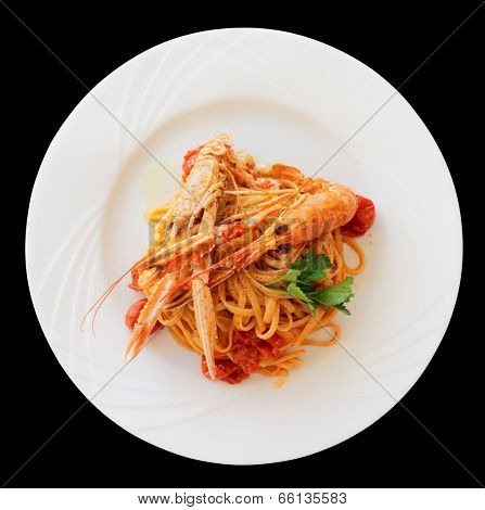 Pasta with tomato sauce and langoustines (scampi) isolated on black