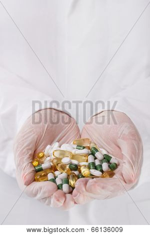 Medicine, pharmacology. Doctor holding heap of pills