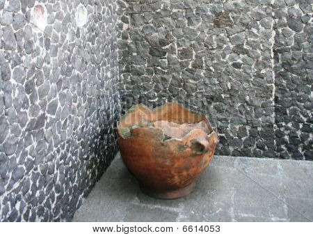 Ancient clay pot against a stone wall