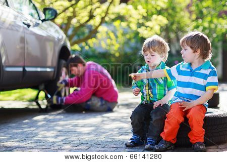 Father And Two Little Boys Repairing Car And Changing Wheel Together