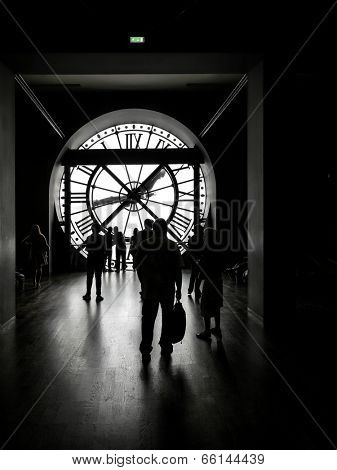 PARIS, FRANCE - AUGUST 25 2013: Silhouettes of tourists visiting d'Orsay Museum shot against big external clock
