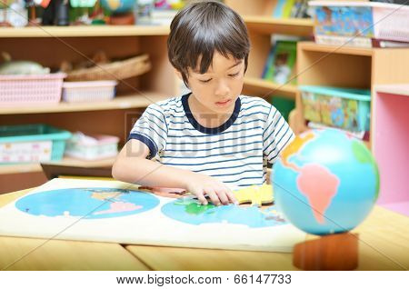 Little Boy Playing With Puzzle Of Map
