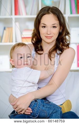 Happy mother breastfeeds her baby at home.
