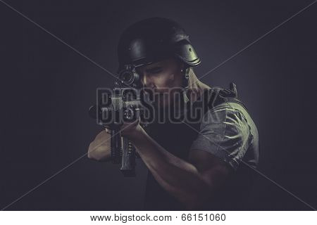 Targeting, paintball sport player wearing protective helmet aiming pistol ,black armor and machine gun