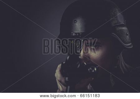 Police, paintball sport player wearing protective helmet aiming pistol ,black armor and machine gun