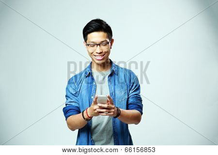 Young happy man using smartphone on gray background