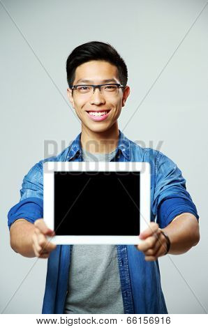 Young happy asian man showing tablet computer screen on gray background