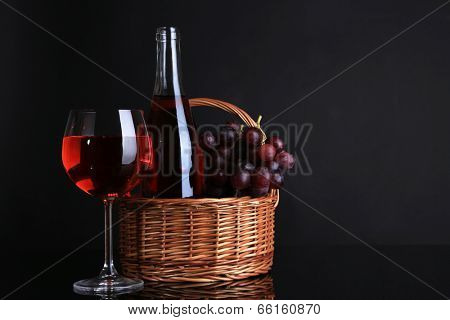Ripe grapes, wine glass and bottle of wine on black background