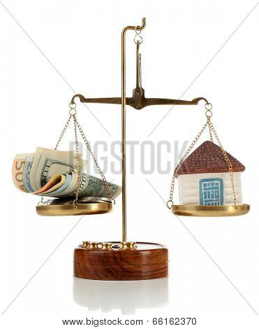 Scale with money and model of house, isolated on white
