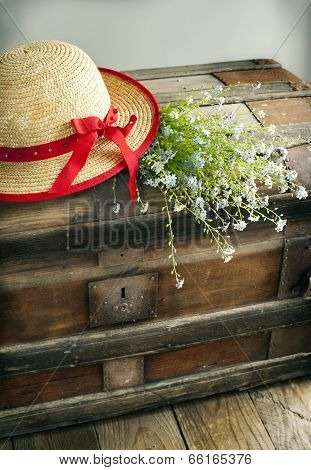 Blue Summer Flowers And Straw Hat On Old Vintage Chest