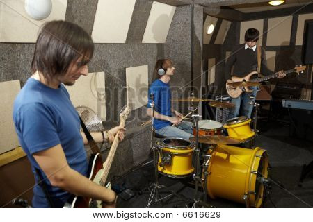 rock band. two musicians with electro guitars and one drummer working in studio