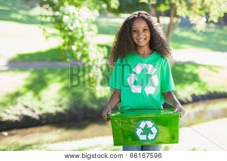 Young environmental activist smiling at the camera holding box on a sunny day
