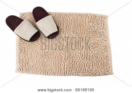 Beige doormat and brown house slippers