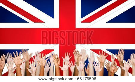 Group Of Multi-Ethnic Arms Outstretched With British Flag As A Background.