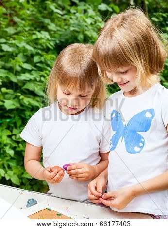 Two little girls are playing with  modelling clay outdoor