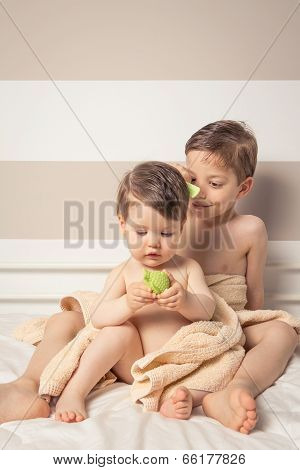 Sweet boy combing little girl in a bed after bath