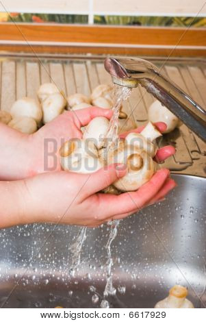 The woman washes mushrooms