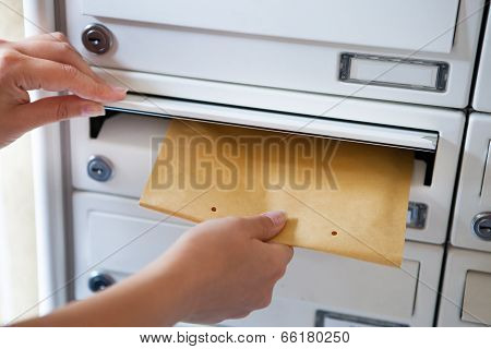 Woman Putting Envelope In Mailbox