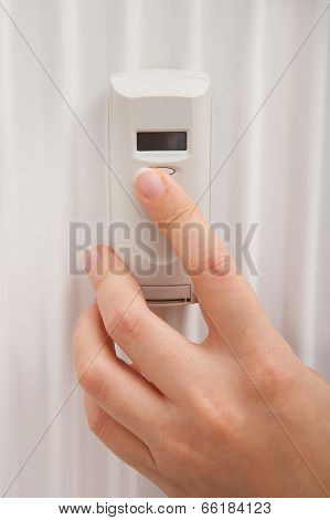 Person's Hand Using Digital Thermostat