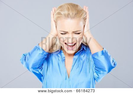 Angry young blond woman closing her ears with her hands and screaming in frustration  isolated on grey